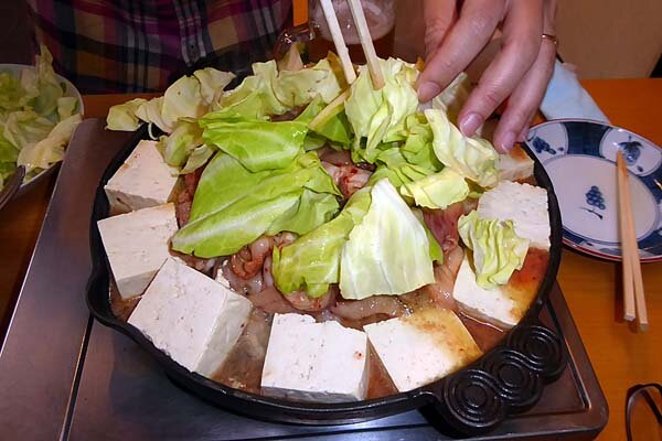 ホルモン幸楽 ホルモンの上に豆腐とキャベツを盛る